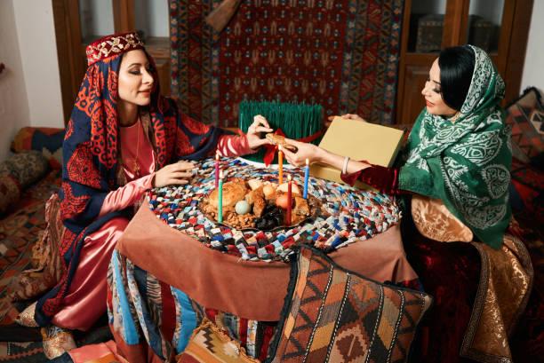 美麗的阿澤裡婦女和諾魯茲託盤與傳統的糕點謝克布拉和帕赫拉瓦圖像檔