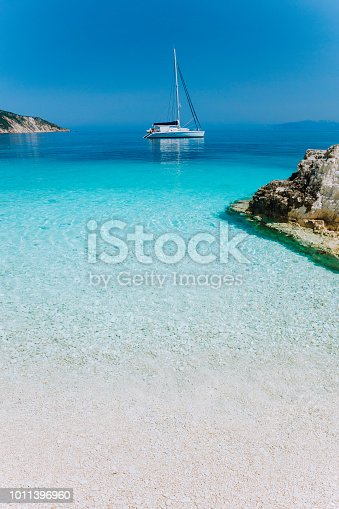Beautiful azure blue lagoon with sailing catamaran yacht boat at anchor. Pure white pebble beach, some rocks in the sea.