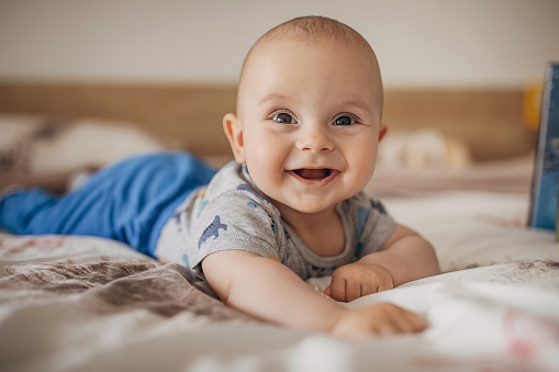 One boy, beautiful baby boy lying on bed and smiling.