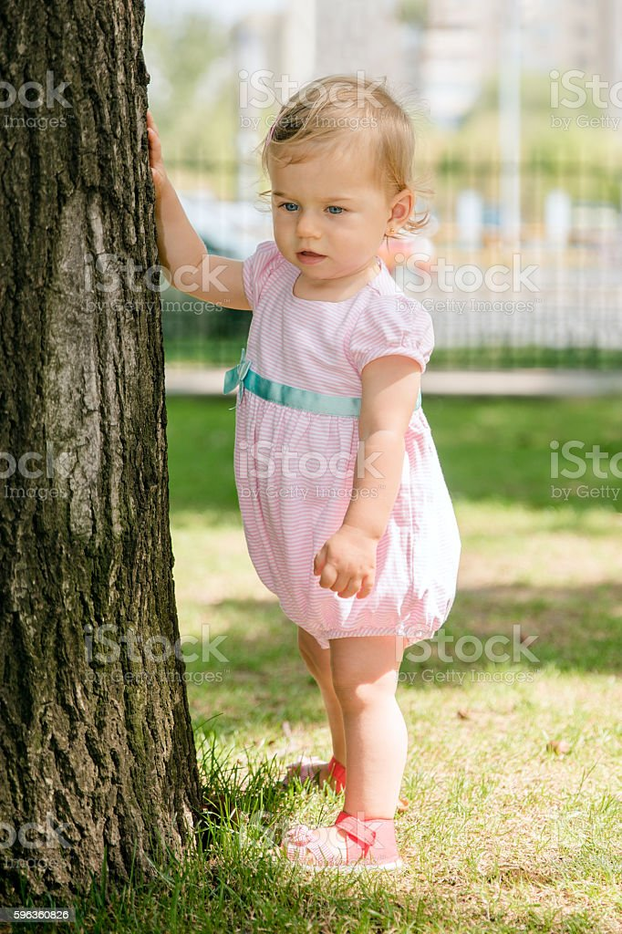 Beautiful baby girl touching a tree royalty-free stock photo