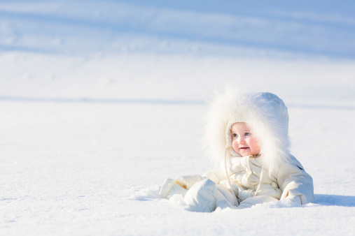 istock Beautiful baby in white suit sitting at snow field 474297959
