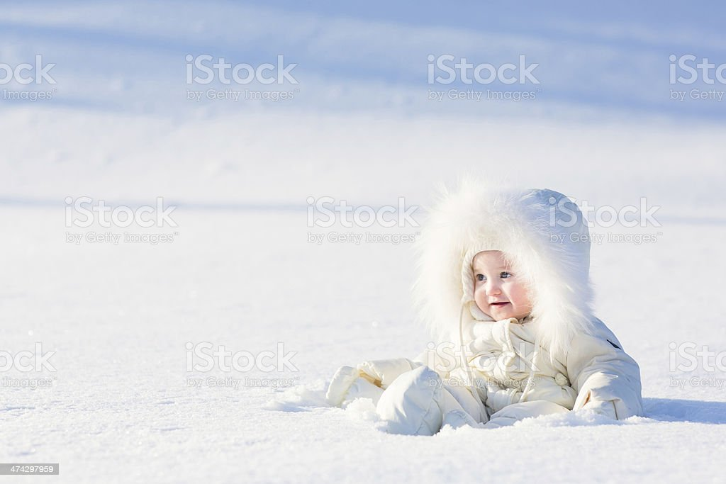 Beautiful baby in white suit sitting at snow field stock photo
