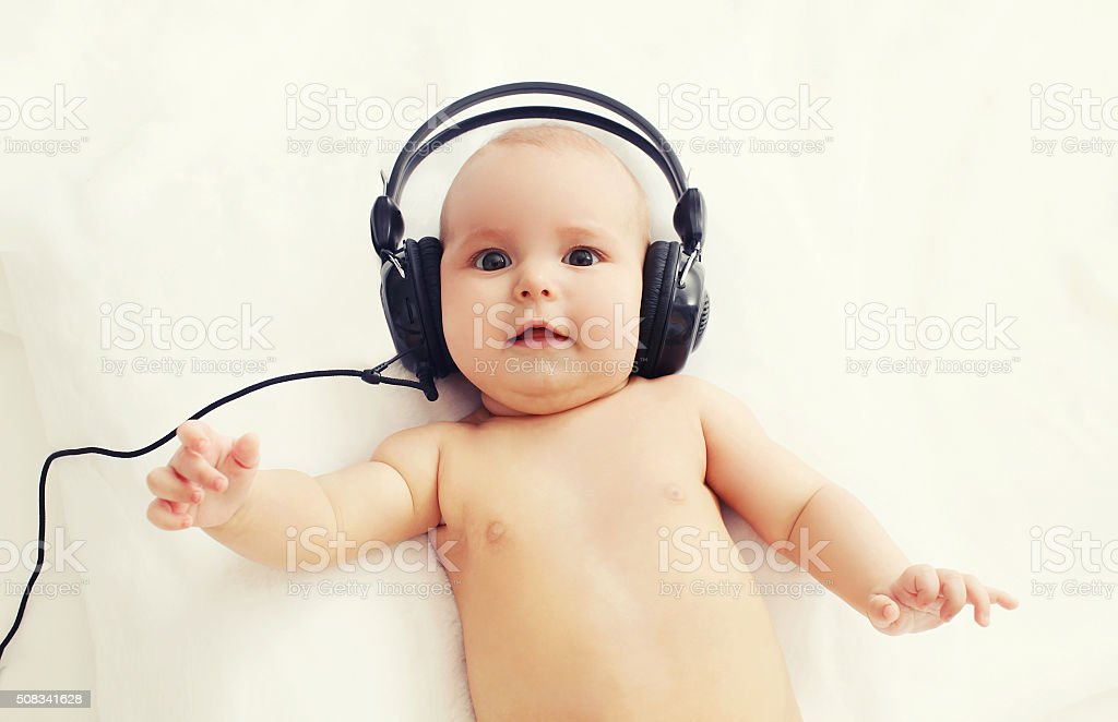 Beautiful baby listens to music in headphones lying on bed stock photo