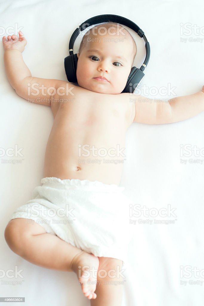 Beautiful Baby on White Towel with Headphone stock photo