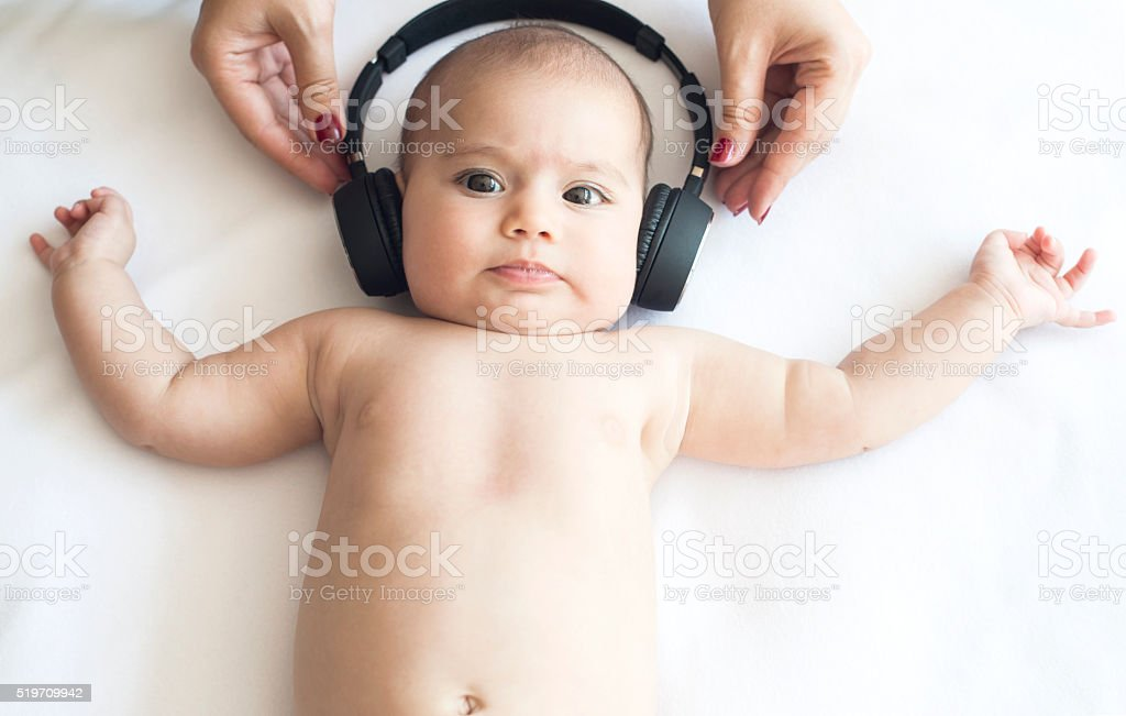 Beautiful Baby on White Towel with Headphone stock photo