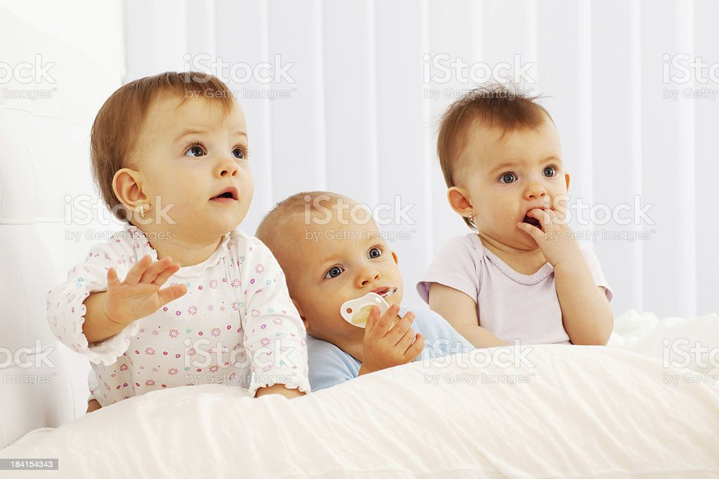 Beautiful baby triplets laying in their bed. stock photo