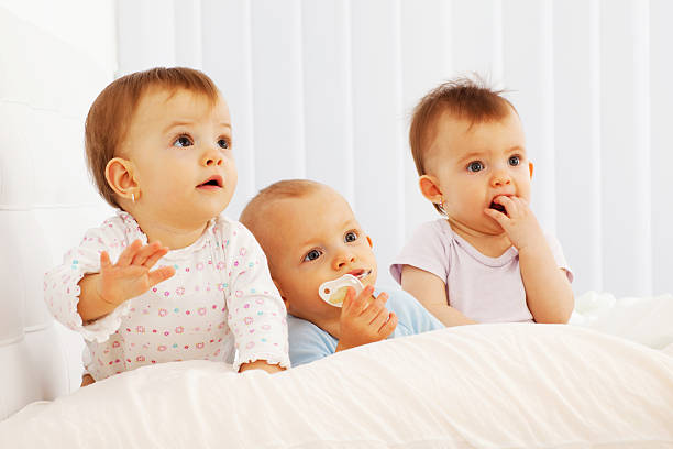 beautiful baby triplets laying in their bed. - triplets stock photos and pictures