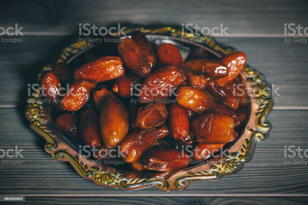 Beautiful background with dried dates on a silver tray on wooden background. The Muslim feast of the holy month of Ramadan Kareem. Free space for your text foto de stock royalty-free