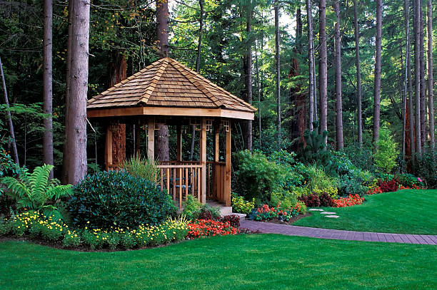 A beautiful backyard garden with a cedar wood gazebo cedar gazebo backyard garden pavilion stock pictures, royalty-free photos & images