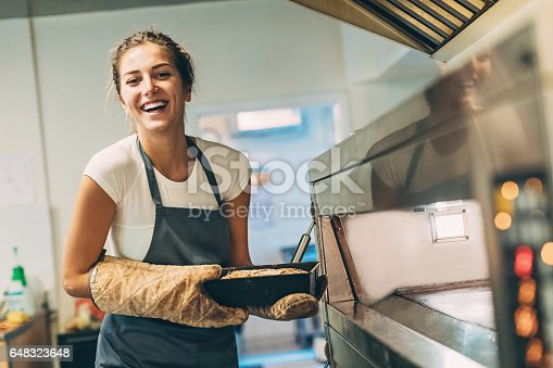 Young baker taking the hot bread out of the stove