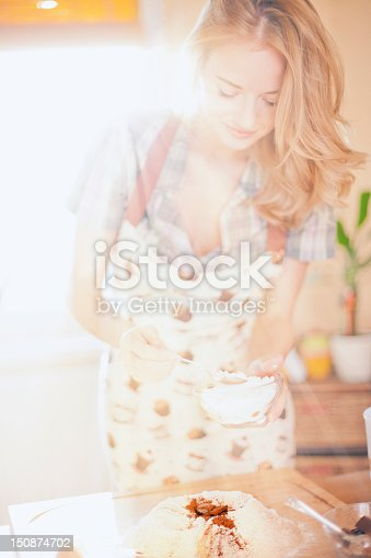 young woman making cake in kitchen