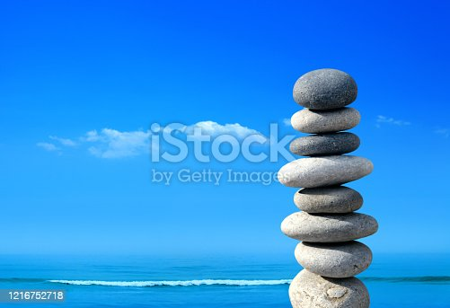Close up pile of stones over sunny blue sky at seaside
