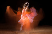 Ballerina dancing on dark stage with ghostly images (single image capture).
