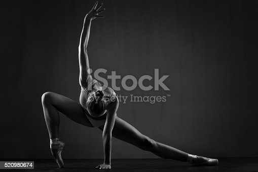Amazing flexible balerina exercising. She has a muscular body and wearing ballet slippers and two parts sport bikini. Her hand is blurred in motion. Black and white photo
