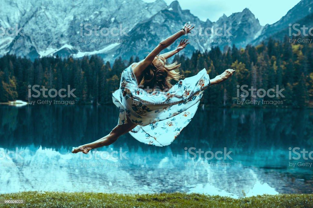 Beautiful ballerina in a dancing jump near the lake stock photo
