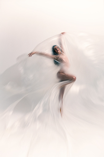 Beautiful ballerina is dancing with thin nylon