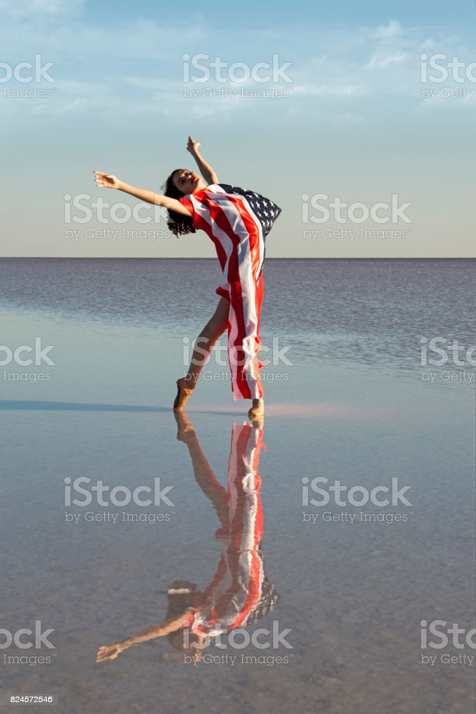 Beautiful ballerina on the water with American Flag a windy day. stock photo