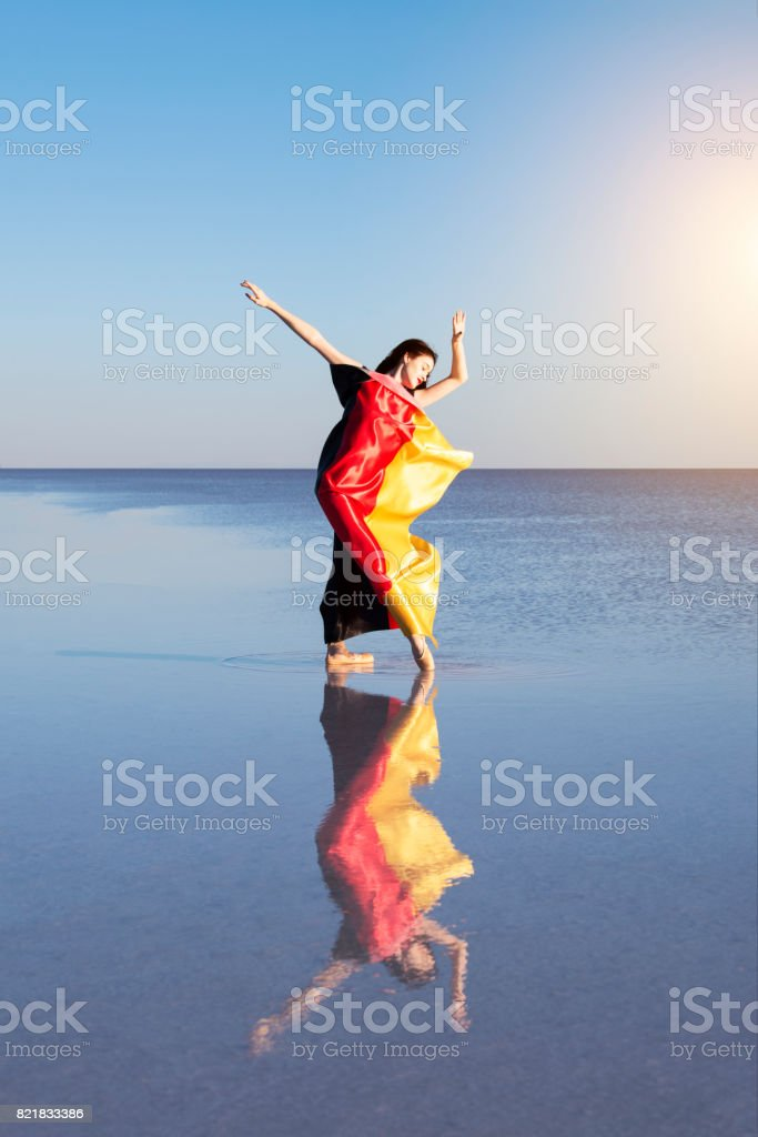 Beautiful ballerina on the water with Germany Flag a windy day. stock photo