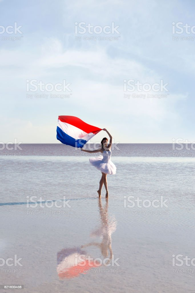 Beautiful ballerina on the water with Netherland Flag a windy day. stock photo
