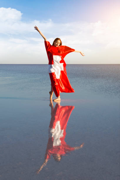 Beautiful ballerina on the water with Swiss Flag a windy day. stock photo