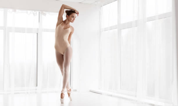 Beautiful Ballerina Standing On Tiptoe In Dance Class Professional Ballet Dancer Dancing On Tiptoe In White Dance Studio. Full Length Portrait. Empty Space nude women pics stock pictures, royalty-free photos & images