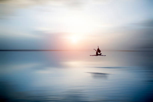 beautiful ballerine jumping and  dancing on the lake in the evening - jumping into water stock pictures, royalty-free photos & images