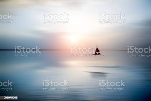 Photo of Beautiful ballerine jumping and  dancing on the lake in the evening