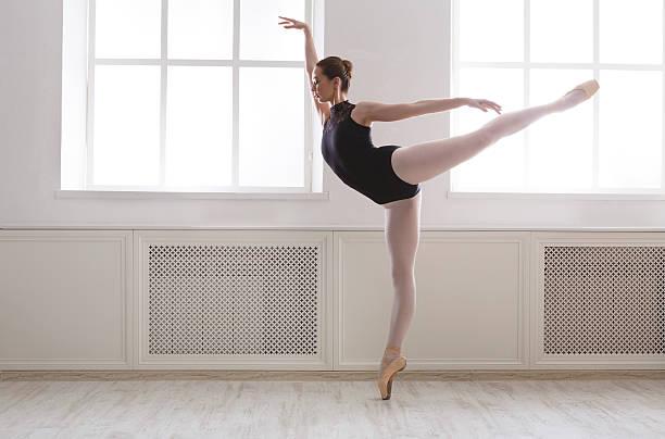 Beautiful ballerine stands in arabesque ballet position stock photo