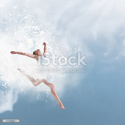 istock Beautiful ballet dancer jumping with cloud of powder 862277268
