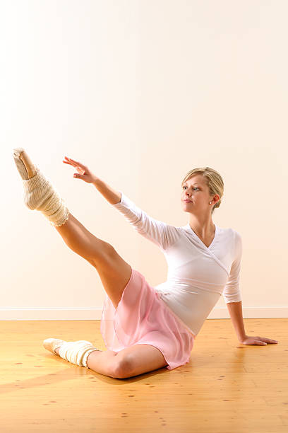 Beautiful ballet dancer lifting arm towards leg stock photo