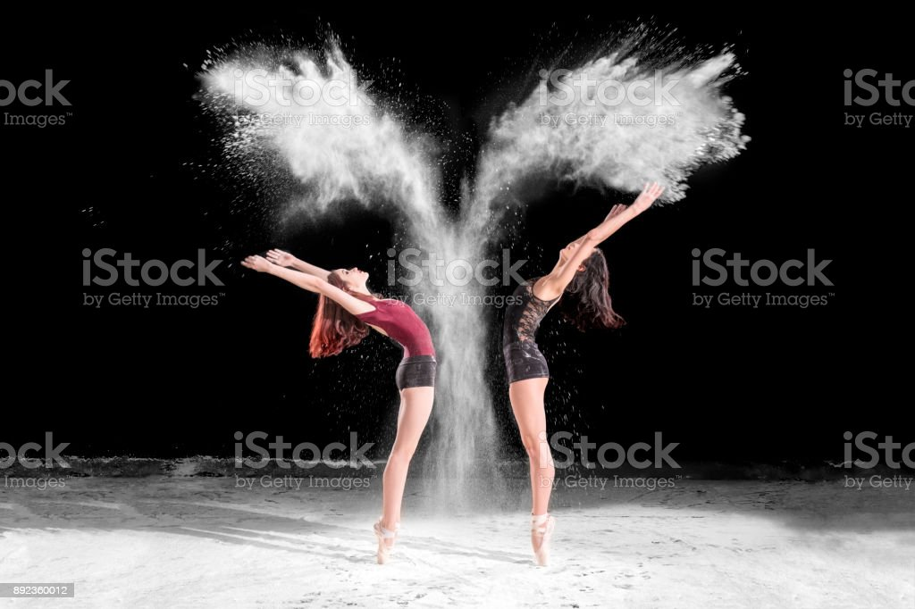Beautiful ballet dancers, dancing with powder on stage stock photo