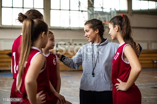 Beautiful female coach embracing teenage girls at basketball court, talking with them about next game strategy