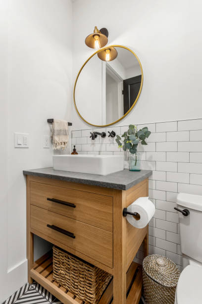 Beautiful bathroom interior in new luxury home with vanity, mirror, and cabinets stock photo