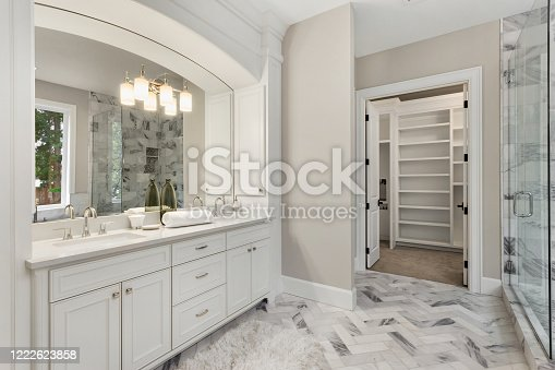 bathroom with beautiful circular mirror and hardwood vanity
