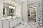 bathroom with beautiful circular mirror and hardwood vanity