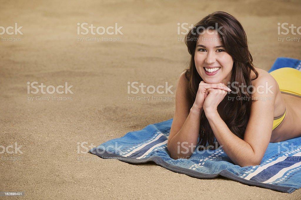 Beautiful beach girl lying on the sand stock photo