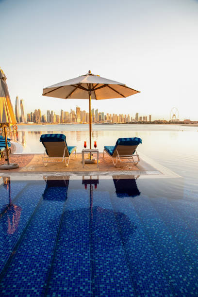 Beautiful beach in Dubai with 2 sun chairs and an umbrella. In the background is the skyline of Dubai Marina stock photo