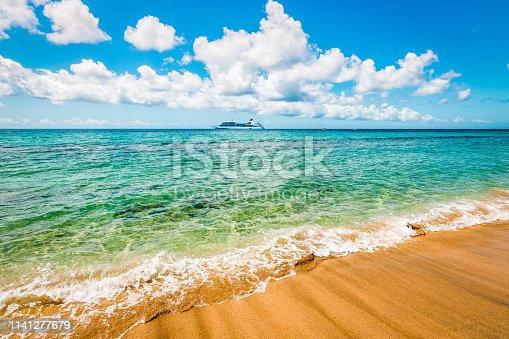 Bright image with turquoise blue ocean and nice Carambola beach on a beautiful summer day. Cruise ship in the distance. Saint Kitts in the Caribbean.