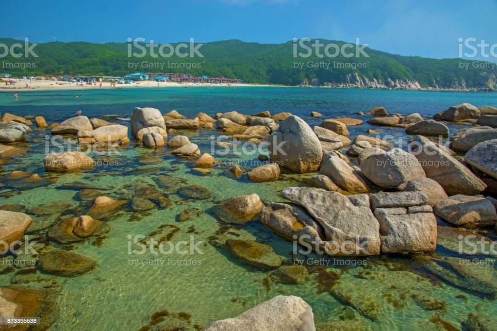 beautiful beach lots of high stones from the destroyed rocks, trees grow. stock photo
