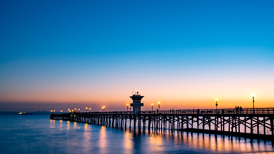 Beautiful Beach Pier at sunset; peaceful water and wooden bridge