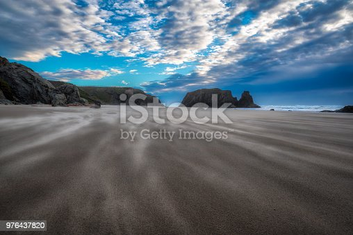 Beautiful beach scene in Bandon Oregon with clouds and blue sky and wind being blown across the surface