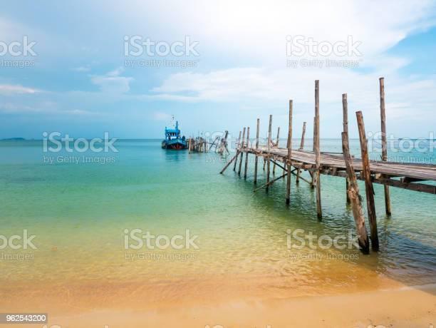 Foto de Bela Praia Com Céu Azul E Um Barco No Cais e mais fotos de stock de Areia