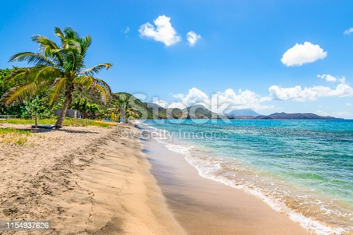 White sandy beach with palm tree and blue sky with white clouds in Saint Kitts, Caribbean.
