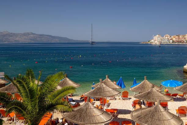 vacker strand med parasoller för en semester i albanien. joniska havet - golf sommar skugga bildbanksfoton och bilder