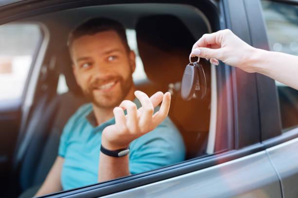 schöne bärtiger mann empfangen autoschlüssel - mietwagen stock-fotos und bilder