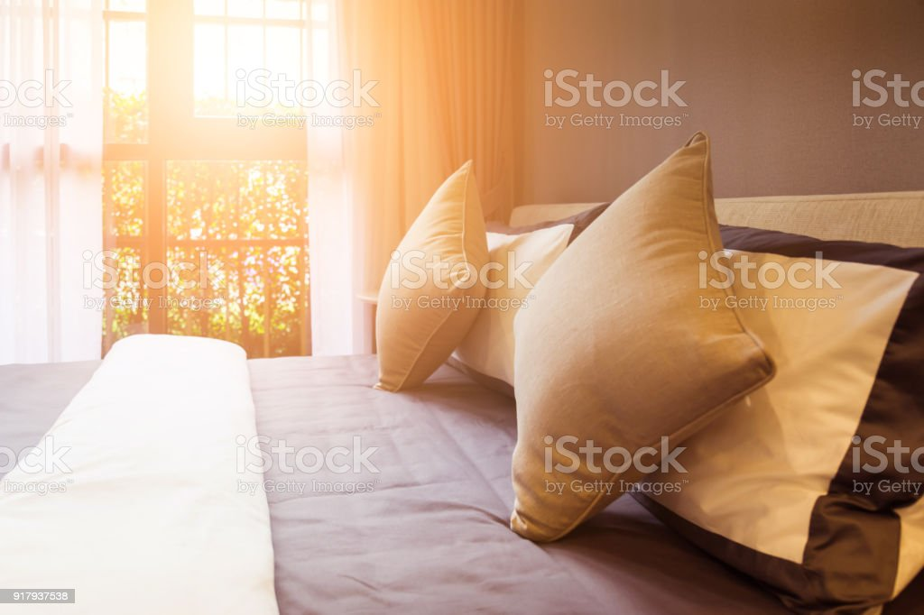 beautiful Bed maid-up with clean white pillows and bed sheets in...