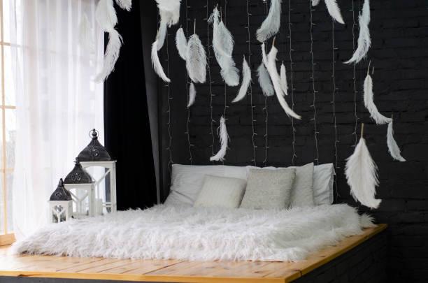 schönes bett in der nähe ein großes fenster und mit federn an der decke. - marineblau schlafzimmer stock-fotos und bilder