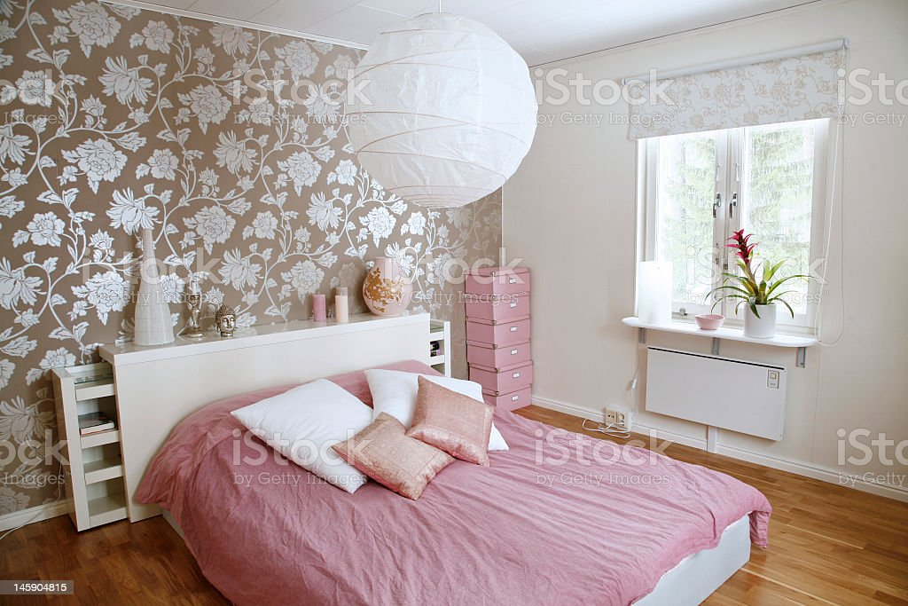 A beautiful bedroom with floral wall and pink bed sheets stock photo