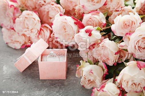 a1c004bf726d 977522134istock Hermosas rosas color beiges con anillo de bodas en mesa de  madera gris 977513844