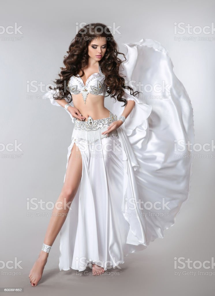 Beautiful belly dancer woman in white shining costume. stock photo